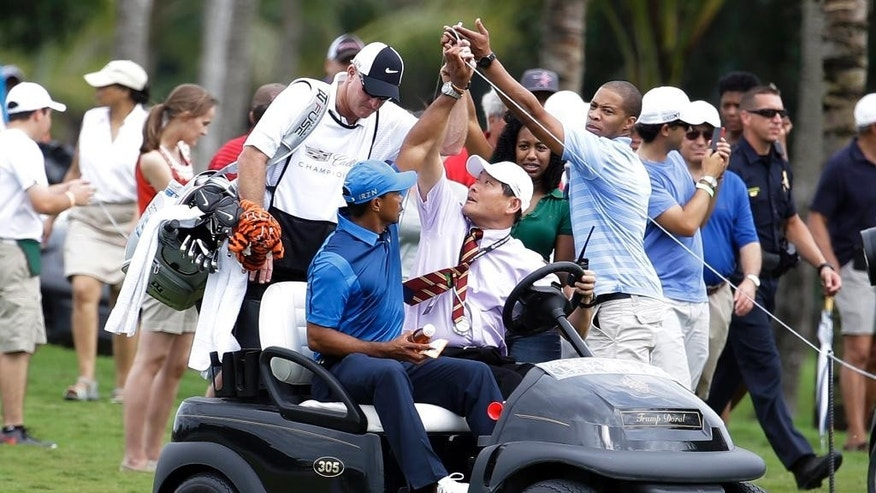 A spectator lifts up a rope as Tiger Woods, left, rides in a cart with his caddy Joe LaCava, center, after play was suspended due to approaching inclement weather during the first round of the Cadillac Championship golf tournament, Thursday, March 6, 2014, in Doral, Fla. (AP Photo/Lynne Sladky)