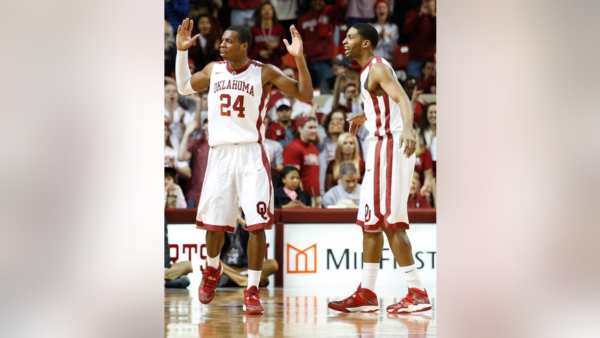 Oklahoma's Buddy Hield (24) and Cameron Clark react during an NCAA college basketball game against West Virginia in Norman, Okla., Wednesday, March 5, 2014. (AP Photo/Garett Fisbeck)
