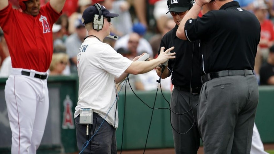Los Angeles Angels' David Freese waits to bat as umpires Hal Gibson and Gerry Davis, right, check an instant replay during an exhibition spring training baseball game Thursday, March 6, 2014, in Tempe, Ariz. On the play, the ruling on the field was confirmed, that Mike Trout was out at home trying to stretch a triple into an inside the park home run. (AP Photo/Morry Gash)