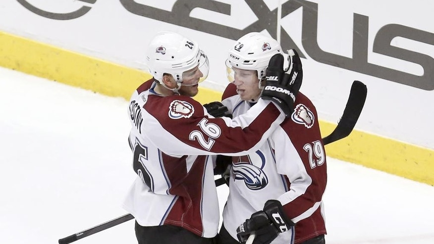 Colorado Avalanche center Paul Stastny (26) celebrates his empty net goal with Nathan MacKinnon (29) during the third period of an NHL hockey game against the Chicago Blackhawks Tuesday, March 4, 2014, in Chicago. The Avalanche won 4-2. (AP Photo/Charles Rex Arbogast)