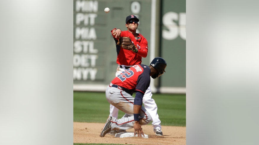Atlanta Braves' Jason Heyward, bottom, is forced out at second base as Boston Red Sox second baseman Dustin Pedroia, top, throws to first during the fourth inning of an exhibition baseball game Friday, March 7, 2014, in Fort, Myers, Fla. The Braves' Justin Upton was safe at first. (AP Photo/Steven Senne)