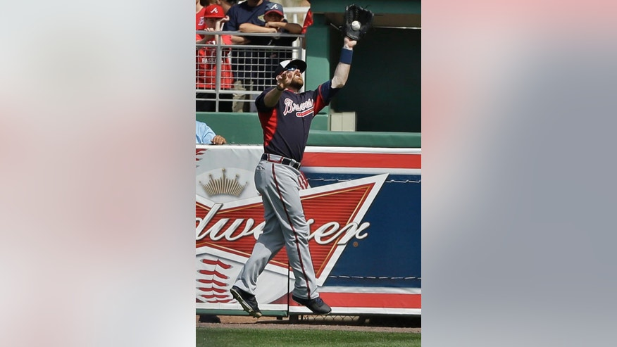 Atlanta Braves' Ryan Doumit catches a fly ball by Boston Red Sox's Will Middlebrooks in the third inning of an exhibition baseball game Friday, March 7, 2014, in Fort, Myers, Fla. (AP Photo/Steven Senne)