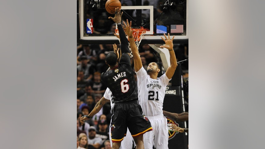 San Antonio Spurs forward Tim Duncan, right, defends Miami Heat forward LeBron James during the first half of an NBA basketball game on Thursday, March 6, 2014, in San Antonio. (AP Photo/Darren Abate)