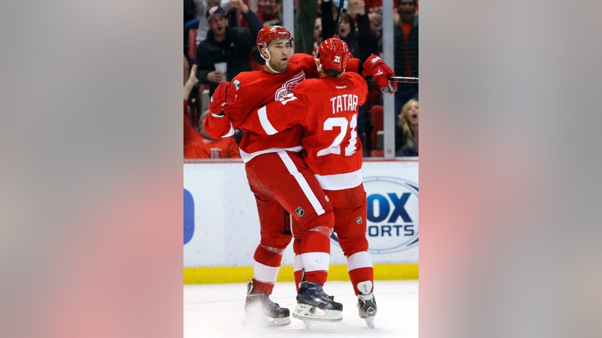 Detroit Red Wings' Kyle Quincey, left, celebrates his second period goal with teammate Tomas Tatar (21), of Czechoslovakia, during an NHL hockey game against the New Jersey Devils Friday, March 7, 2014, in Detroit. (AP Photo/Duane Burleson)