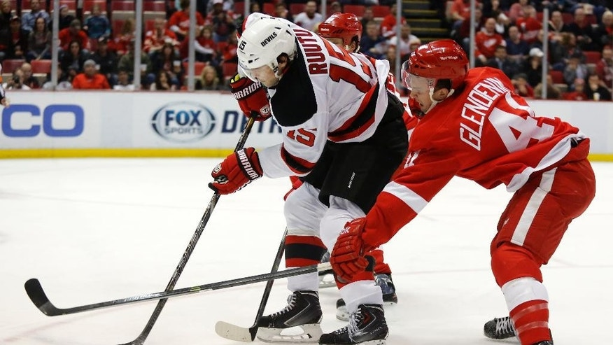 Detroit Red Wings' Luke Glendening (41) tries to block a pass by New Jersey Devils' Tuomo Ruutu (15), of Finland, during the first period of an NHL hockey game Friday, March 7, 2014, in Detroit. (AP Photo/Duane Burleson)