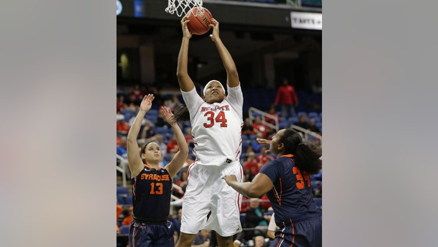 North Carolina State's Markeisha Gatling, center, shoots between Syracuse's Brianna Butler, left, and Shakeya Leary, right, during the first half of an NCAA college basketball game at the Atlantic Coast Conference tournament in Greensboro, N.C., Friday, March 7, 2014. (AP Photo/Chuck Burton)
