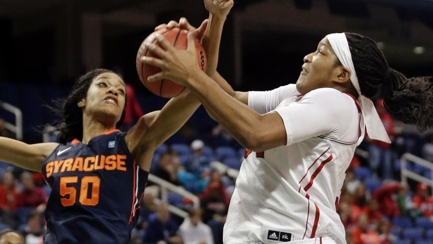North Carolina State's Markeisha Gatling, right, and Syracuse's Briana Day, left, battle for a rebound during the first half of an NCAA college basketball game at the Atlantic Coast Conference tournament in Greensboro, N.C., Friday, March 7, 2014. (AP Photo/Chuck Burton)