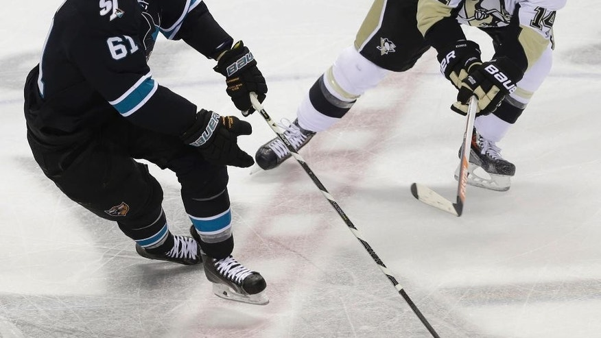 San Jose Sharks' Justin Braun (61) works against Pittsburgh Penguins' Chris Kunitz (14) during the first period of an NHL hockey game on Thursday, March 6, 2014, in San Jose, Calif. (AP Photo/Marcio Jose Sanchez)