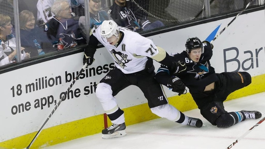 Pittsburgh Penguins' Evgeni Malkin (71) of Russia, collides against the boards with San Jose Sharks' Justin Braun (61) during the first period of an NHL hockey game on Thursday, March 6, 2014, in San Jose, Calif. (AP Photo/Marcio Jose Sanchez)