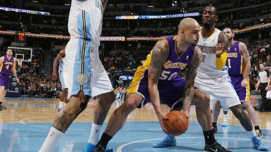 Los Angeles Lakers center Robert Sacre, center, picks up loose ball as Denver Nuggets forwards Wilson Chandler, left, and J.J. Hickson cover in the first quarter of an NBA basketball game in Denver on Friday, March 7, 2014. (AP Photo/David Zalubowski)
