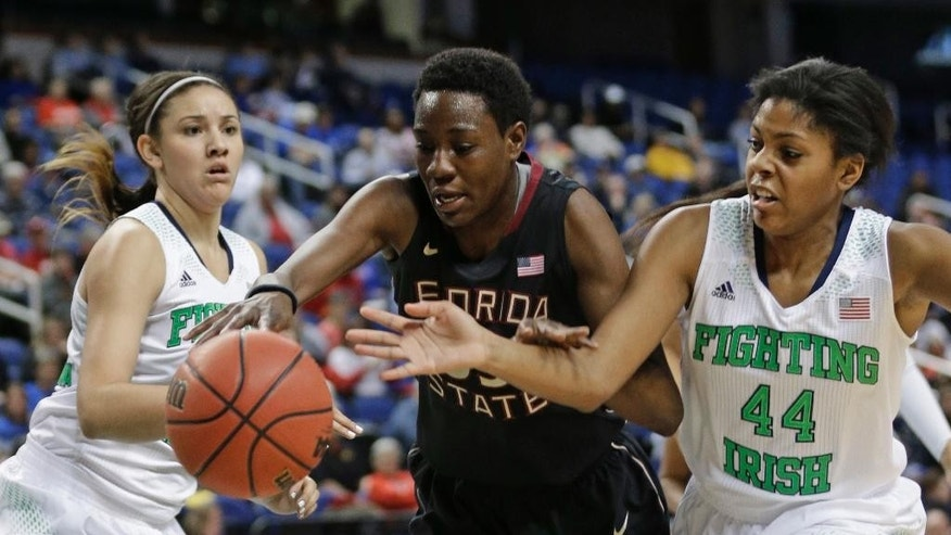 Florida State's Natasha Howard, center, battles Notre Dame's Ariel Braker, right, and Natalie Achonwa, left, for a loose ball during the first half of an NCAA college basketball game at the Atlantic Coast Conference tournament in Greensboro, N.C., Friday, March 7, 2014. (AP Photo/Chuck Burton)