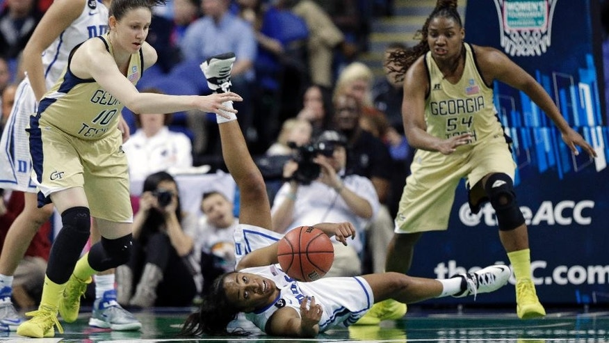 Duke's Oderah Chidom, center, passes the ball as Georgia Tech's Katarina Vuckovic, left, and Roddreka Rogers, right, defend during the first half of an NCAA college basketball game at the Atlantic Coast Conference tournament in Greensboro, N.C., Friday, March 7, 2014. (AP Photo/Chuck Burton)
