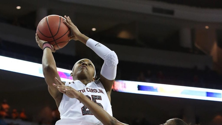 South Carolina guard Tiffany Mitchell (25) takes a shot against Georgia guard Khaalidah Miller (1) in the first half of a quarterfinal women's Southeastern Conference tournament NCAA college basketball game Friday, March 7, 2014, in Duluth, Ga.  (AP Photo/Jason Getz)