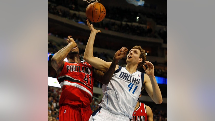 Portland Trail Blazers forward Thomas Robinson, left, and Dallas Mavericks forward Dirk Nowitzki, right, of Germany, fight for a loose ball during the first half of an NBA basketball game on Friday, March 7, 2014, in Dallas. (AP Photo/John F. Rhodes)