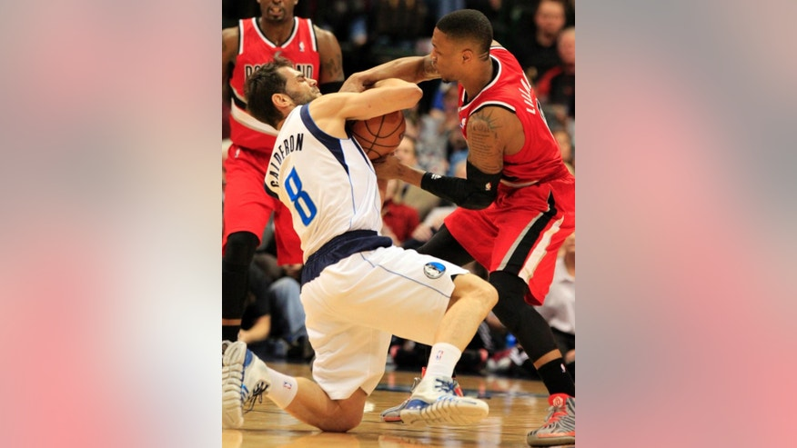Dallas Mavericks guard Jose Calderon (8), of Spain, and Portland Trail Blazers guard Damian Lillard (0) battle for the ball during the first half of an NBA basketball game on Friday, March 7, 2014, in Dallas. (AP Photo/John F. Rhodes)