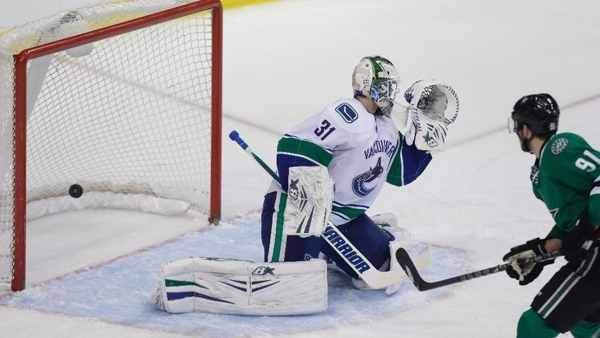 Dallas Stars center Tyler Seguin (91) scores a goal against Vancouver Canucks goalie Eddie Lack (31) during the first period of an NHL hockey game Thursday, March 6, 2014, in Dallas. (AP Photo/LM Otero)