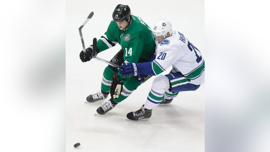 Dallas Stars left wing Jamie Benn (14) and Vancouver Canucks left wing Chris Higgins (20) skate for the puck during the first period of an NHL hockey game Thursday, March 6, 2014, in Dallas. (AP Photo/LM Otero)