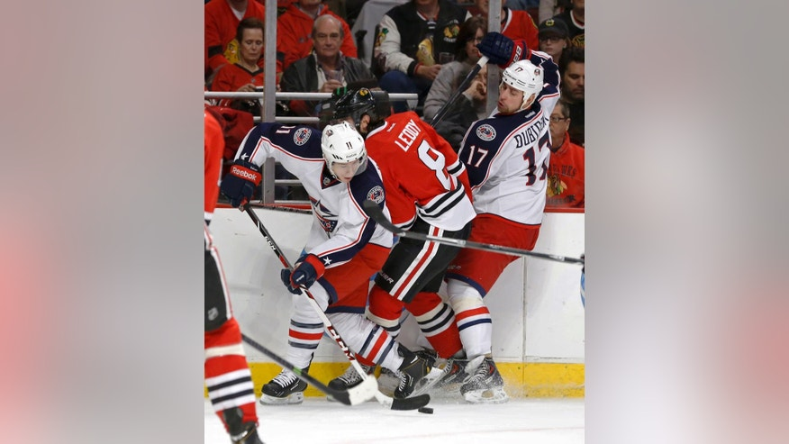 Columbus Blue Jackets left wing Matt Calvert (11) spins out of a check by Chicago Blackhawks defenseman Nick Leddy (8) as Brandon Dubinsky (17) watches during the first period of an NHL hockey game Thursday, March 6, 2014, in Chicago. (AP Photo/Charles Rex Arbogast)