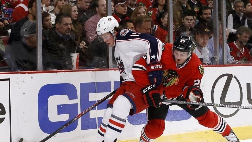 Columbus Blue Jackets center Ryan Johansen, left, keeps Chicago Blackhawks left wing Brandon Saad (20) away from the puck during the first period of an NHL hockey game Thursday, March 6, 2014, in Chicago. (AP Photo/Charles Rex Arbogast)