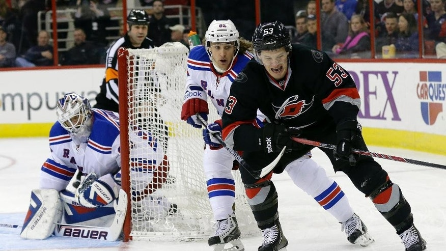 Carolina Hurricanes' Jeff Skinner (53) chases the puck as New York Rangers' Carl Hagelin (62) and goalie Henrik Lundqvist, of Sweden, defend the goal during the second period of an NHL hockey game in Raleigh, N.C., Friday, March 7, 2014. (AP Photo/Gerry Broome)