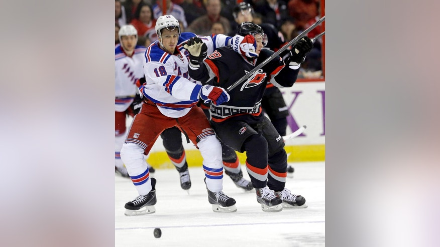 New York Rangers' Marc Staal (18) and Carolina Hurricanes' Alexander Semin (28) chase the puck during the second period of an NHL hockey game in Raleigh, N.C., Friday, March 7, 2014. (AP Photo/Gerry Broome)
