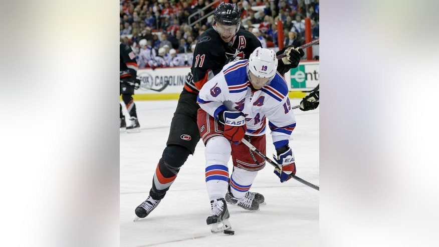 Carolina Hurricanes' Jordan Staal (11) and New York Rangers' Brad Richards (19) chase the puck during the second period of an NHL hockey game in Raleigh, N.C., Friday, March 7, 2014. (AP Photo/Gerry Broome)
