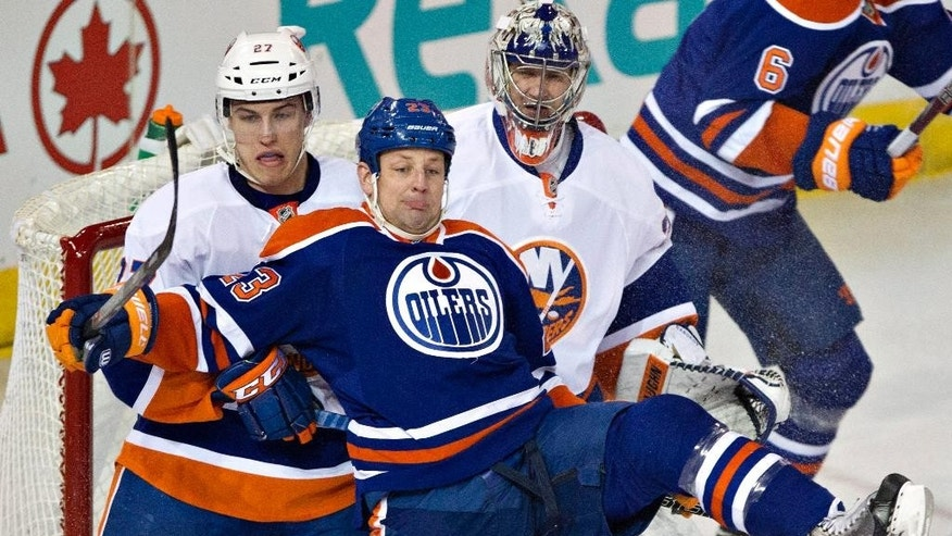 New York Islanders' Anders Lee (27) and goalie Evgeni Nabokov (20) keep Edmonton Oilers' Matt Hendricks (23) off-balance during the first period of an NHL hockey game in Edmonton, Alberta, on Thursday, March 6, 2014. (AP Photo/The Canadian Press, Jason Franson)