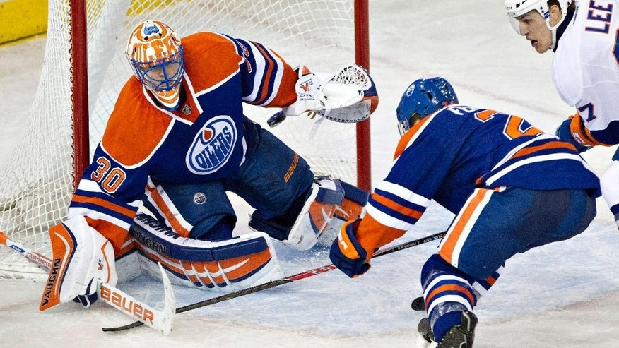 New York Islanders' Anders Lee (27) and Edmonton Oilers' Andrew Ference (21) look for the rebound as Oilers goalie Ben Scrivens (30) makes a save during the second period of an NHL hockey game in Edmonton, Alberta, on Thursday, March 6, 2014. (AP Photo/The Canadian Press, Jason Franson)