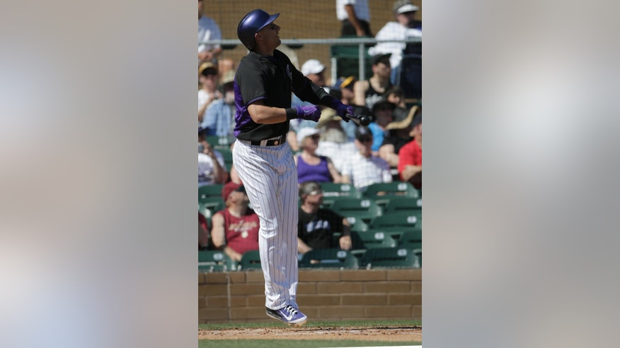 Colorado Rockies' Troy Tulowitzki watches his solo home run against the Los Angeles Angels during the first inning of a spring training baseball game in Scottsdale, Ariz., Friday, March 7, 2014. (AP Photo/Chris Carlson)