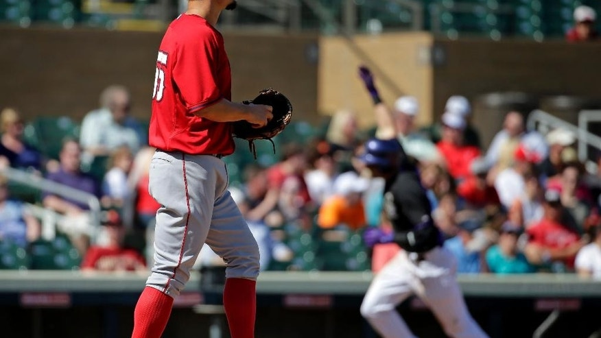 Colorado Rockies' Troy Tulowitzki celebrates a two-run home run as Los Angeles Angels starting pitcher Joe Blanton looks on during the third inning of a spring training baseball game in Scottsdale, Ariz., Friday, March 7, 2014. (AP Photo/Chris Carlson)