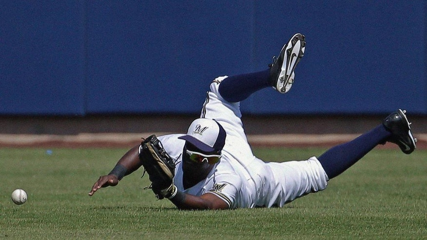 Milwaukee Brewers' Elian Herrera cannot catch a ball hit by San Diego Padres' Xavier Nady during the first inning of an exhibition spring training baseball game on Friday, March 7, 2014, in Phoenix. (AP Photo/Morry Gash)
