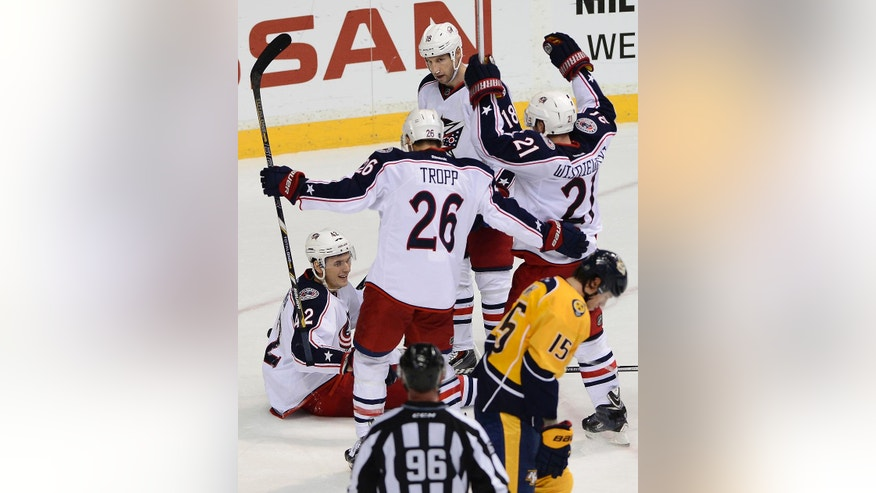 Columbus Blue Jackets center Artem Anisimov, left,  of Russia, celebrates with teammates Corey Tropp (26), James Wisniewski (21) and R. J. Umberger (18) after scoring against the Nashville Predators in the third period of an NHL hockey game on Saturday, March 8, 2014, in Nashville, Tenn. Predators forward Craig Smith (15) skates by. The Blue Jackets won 1-0. (AP Photo/Mark Zaleski)