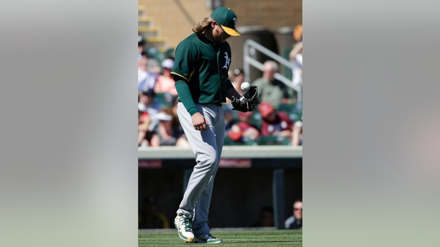 Oakland Athletics starting pitcher A.J. Griffin walks back to the mount after giving up the third run against the Colorado Rockies during the first  inning of a spring training baseball game in Scottsdale, Ariz., Saturday, March 8, 2014. (AP Photo/Chris Carlson)