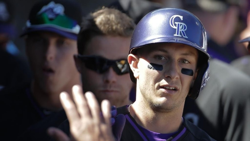 Colorado Rockies' Troy Tulowitzki celebrates in the dugout after scoring during the first inning of a spring training baseball game against the Oakland Athletics in Scottsdale, Ariz., Saturday, March 8, 2014. (AP Photo/Chris Carlson)