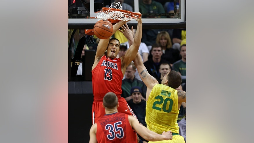 Arizona's Nick Johnson, left, slams a dunk over teammate Kaleb Tarczewski and Oregon's Waverly Austin during the first half of an NCAA college basketball game in Eugene, Ore. on Saturday, March 8, 2014. (AP Photo/Chris Pietsch)