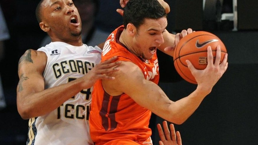 Virginia Tech's' Devin Wilson, right, wrestles a rebound away from Georgia Tech's Kammeon Holsey (24) during the first half of an NCAA college basketball game Saturday, March 8, 2014, in Atlanta. (AP Photo/David Tulis)