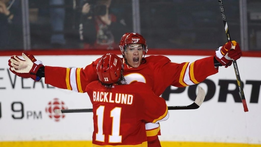 Calgary Flames' Joe Colborne celebrates his game winning goal with teammate Mikael Backlund during third period NHL hockey action against the NY Islanders in Calgary, Alberta, Friday, March 7, 2014. (AP Photo/The Canadian Press, Jeff McIntosh)