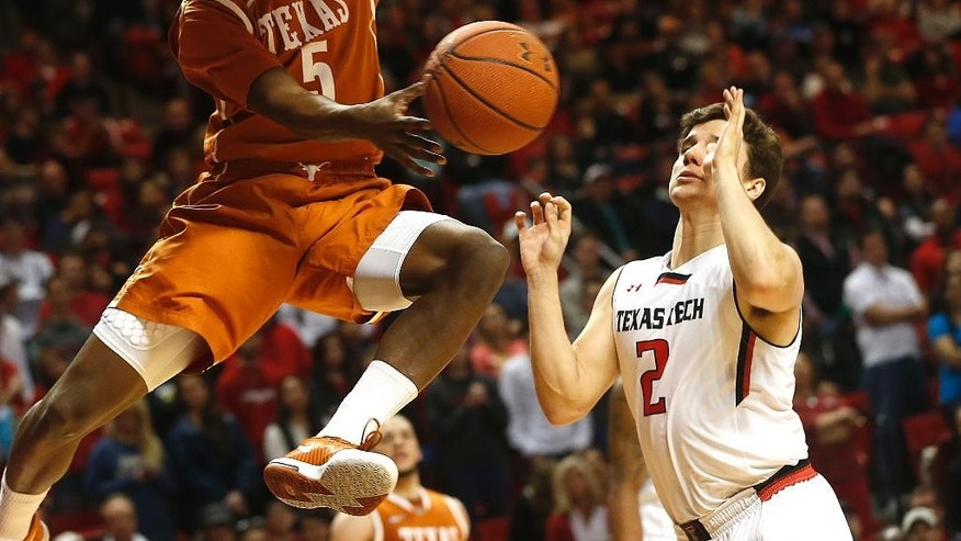 Texas' Damarcus Croaker throws a pass over Texas Tech's Dusty Hannahs (2) during their NCAA college basketball game in Lubbock, Texas, Saturday, Mar, 8, 2014. (AP Photo/Lubbock Avalanche-Journal, Zach Long) ALL LOCAL TV OUT