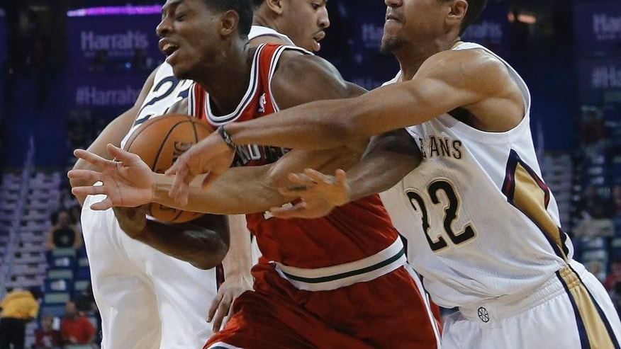 Milwaukee Bucks guard Brandon Knight (11) is fouled by New Orleans Pelicans guard Brian Roberts (22) during the first half of an NBA basketball game in New Orleans, Friday, March 7, 2014. (AP Photo/Bill Haber)