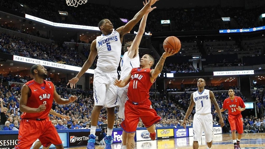 SMU guard Nic Moore (11) goes to the basket against Memphis defenders Nick King (5), Austin Nichols, center, and Joe Jackson (1) in the first half of an NCAA college basketball game Saturday, March 8, 2014, in Memphis, Tenn. (AP Photo/Lance Murphey)