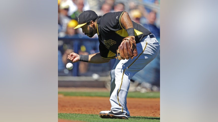 Pittsburgh Pirates third baseman Pedro Alvarez (24) bobbles an infield single by Tampa Bay Rays Evan Longoria in the first inning of a exhibition baseball game in Port Charlotte, Fla., Saturday, March 8, 2014. (AP Photo/Gerald Herbert)