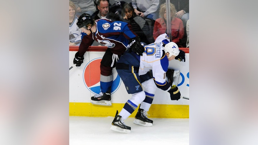 St. Louis Blues defenseman Jay Bouwmeester, right, checks Colorado Avalanche left wing Gabriel Landeskog, left, into the boards in the first period of an NHL hockey game on Saturday, March 8, 2014, in Denver. (AP Photo/Chris Schneider)