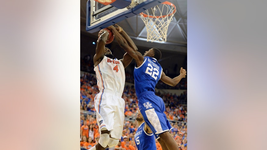 Florida center Patric Young (4) goes to the basket but is blocked by Kentucky forward Alex Poythress (22) during the first half of an NCAA college basketball game Saturday, March 8, 2014 in Gainesville, Fla.  (AP Photo/Phil Sandlin)