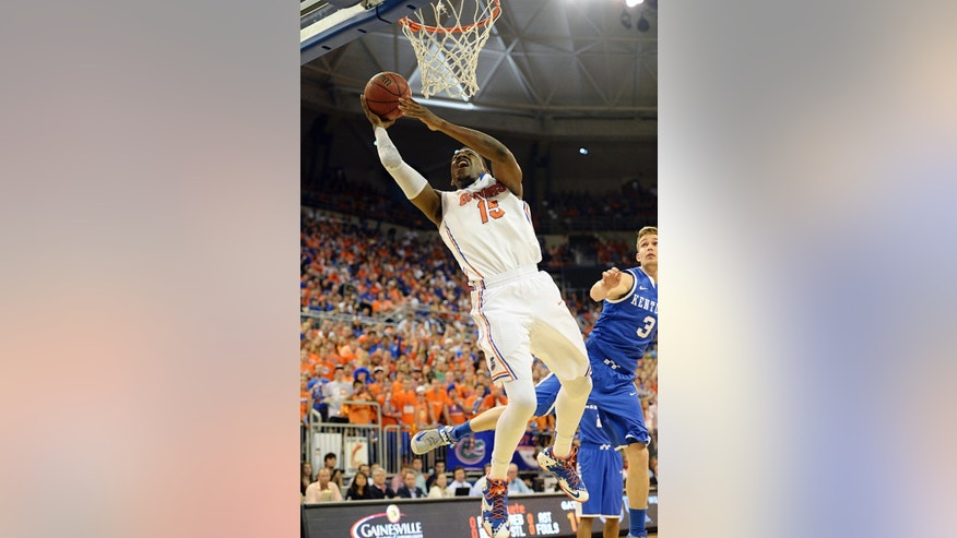Florida forward Will Yeguete (15) goes for the basket as Kentucky guard Jarrod Polson (3) watches during the first half of an NCAA college basketball game Saturday, March 8, 2014, in Gainesville, Fla.  (AP Photo/Phil Sandlin)