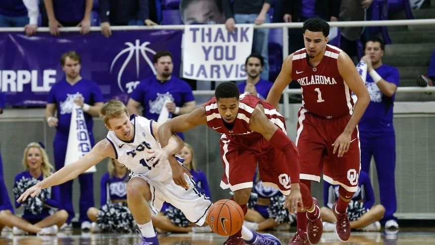 TCU guard Christian Gore (13) and Oklahoma guard Isaiah Cousins scramble for a loose ball in the first half of an NCAA basketball game Saturday, March 8, 2014, in Fort Worth, Texas. (AP Photo/Sharon Ellman)