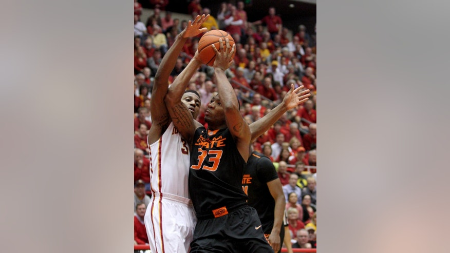 Oklahoma State guard Marcus Smart draws a foul on Iowa State forward Melvin Ejim as he drives to the basket during the second half of an NCAA college basketball game in Ames, Iowa, Saturday, March 8, 2014. Iowa State won 85-81 in overtime. (AP Photo/Justin Hayworth)