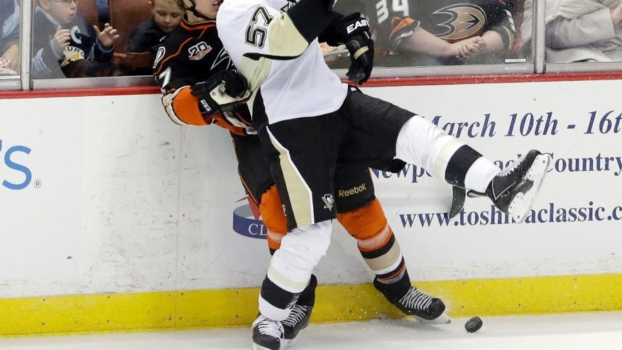 Anaheim Ducks defenseman Hampus Lindholm (47), of Sweden, and Pittsburgh Penguins center Marcel Goc (57), of Germany, tangle in the first period of an NHL hockey game in Anaheim, Calif., Friday, March 7, 2014.  (AP Photo/Reed Saxon)