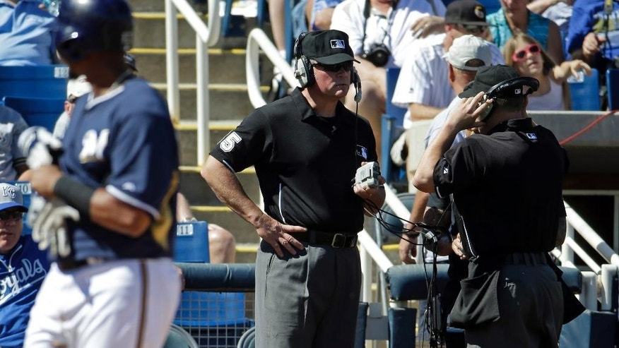 Umpires Ted Barrett, left, and Alan Bailey review a call during an exhibition spring training baseball game between the Milwaukee Brewers and the Kansas City Royals Saturday, March 8, 2014, in Phoenix. (AP Photo/Morry Gash)