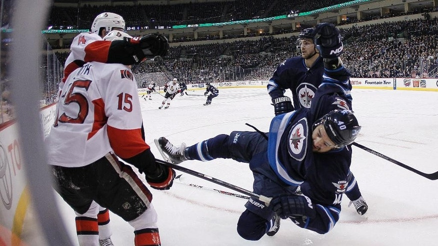 Winnipeg Jets' Devin Setoguchi (40) gets leveled by Ottawa Senators' Chris Phillips (4) as Senators' Zack Smith (15) and Jets Michael Frolik (67) look on during the second period of an NHL hockey game, Saturday, March 8, 2014 in Winnipeg, Manitoba. (AP Photo/The Canadian Press, John Woods)