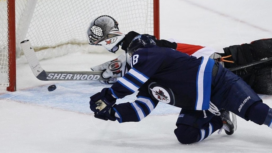 Winnipeg Jets' Bryan Little (18) dives for the puck to make the shot and score on Ottawa Senators' goaltender Craig Anderson (41) during the first period of an NHL hockey game, Saturday, March 8, 2014 in Winnipeg, Manitoba. (AP Photo/The Canadian Press, John Woods)